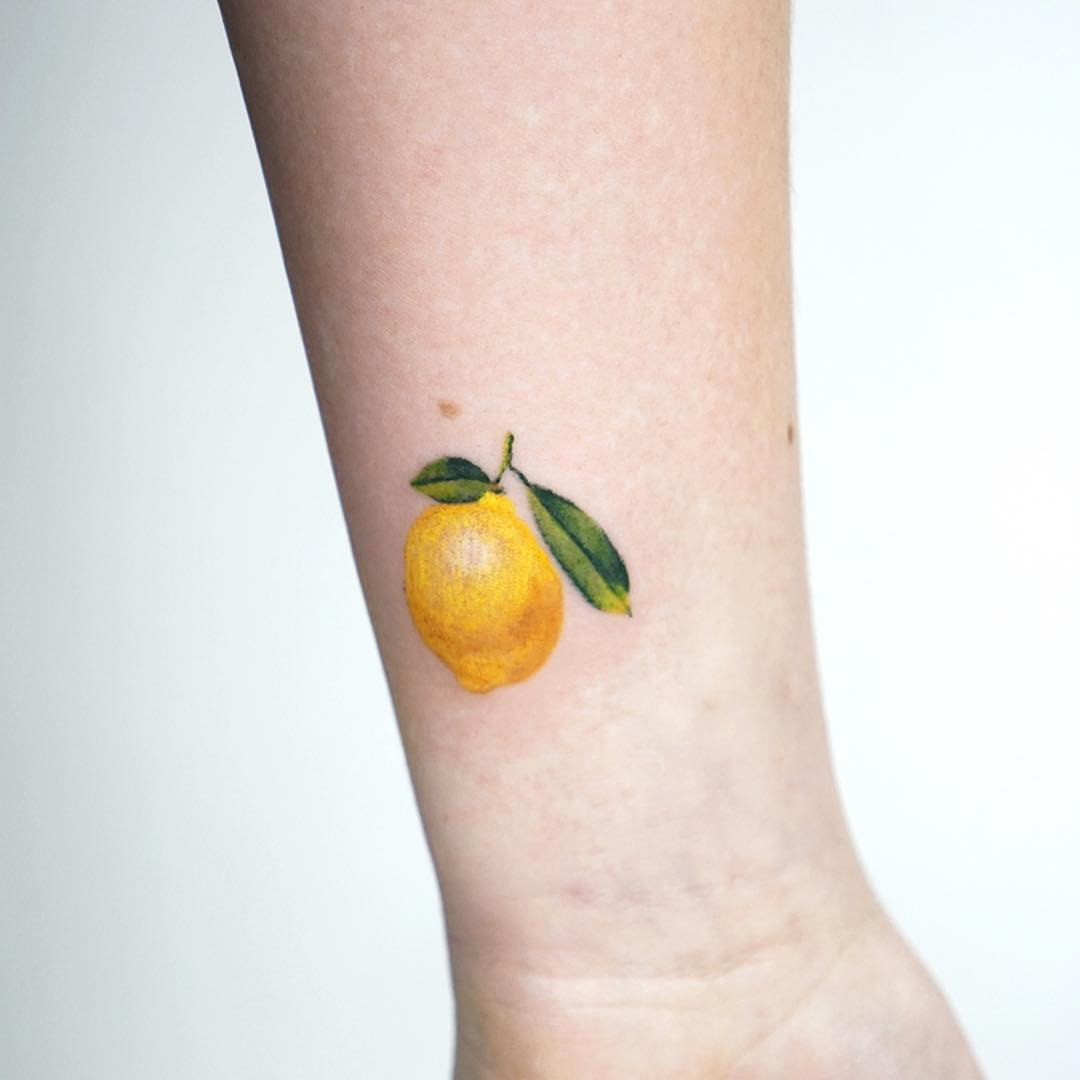 Tiny lemon tattoo by tattooist picsola