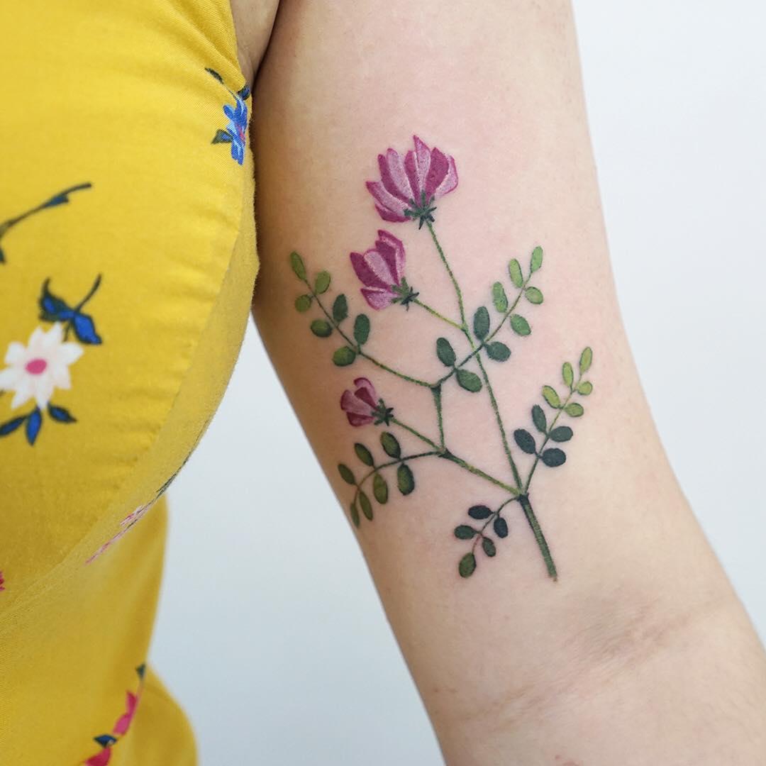 Vicia flower tattoo by tattooist picsola