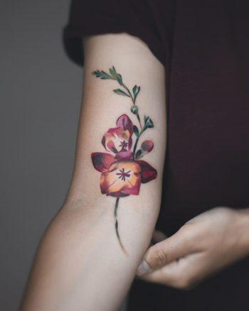 Watercolor flower tattoo by Rey Jasper