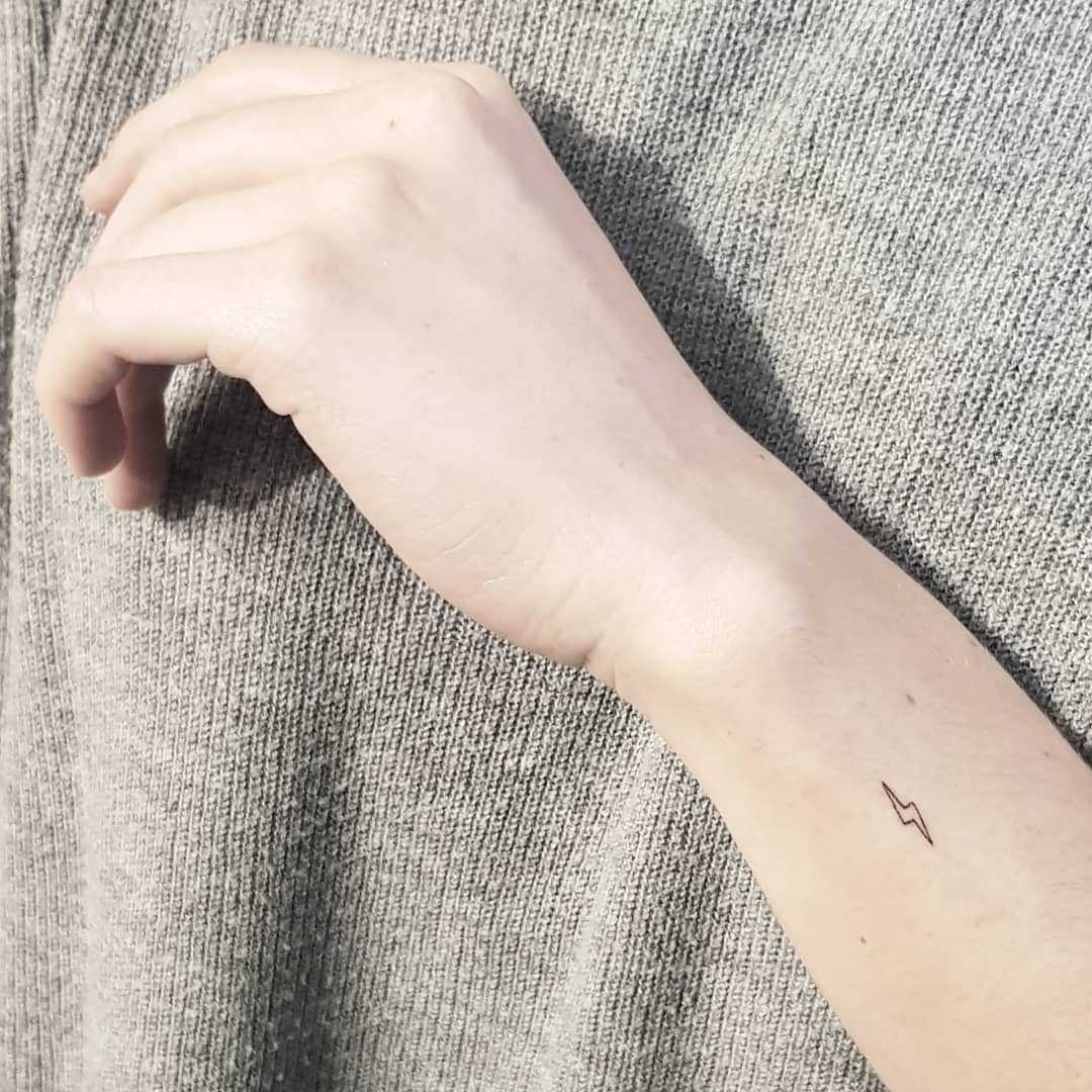 Micro lightning bolt tattoo by Melanie Benyahya