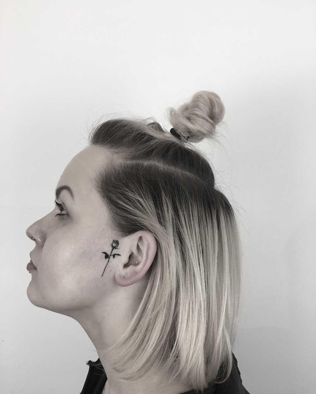 Rose tattoo next to the ear by Krzysztof Szeszko