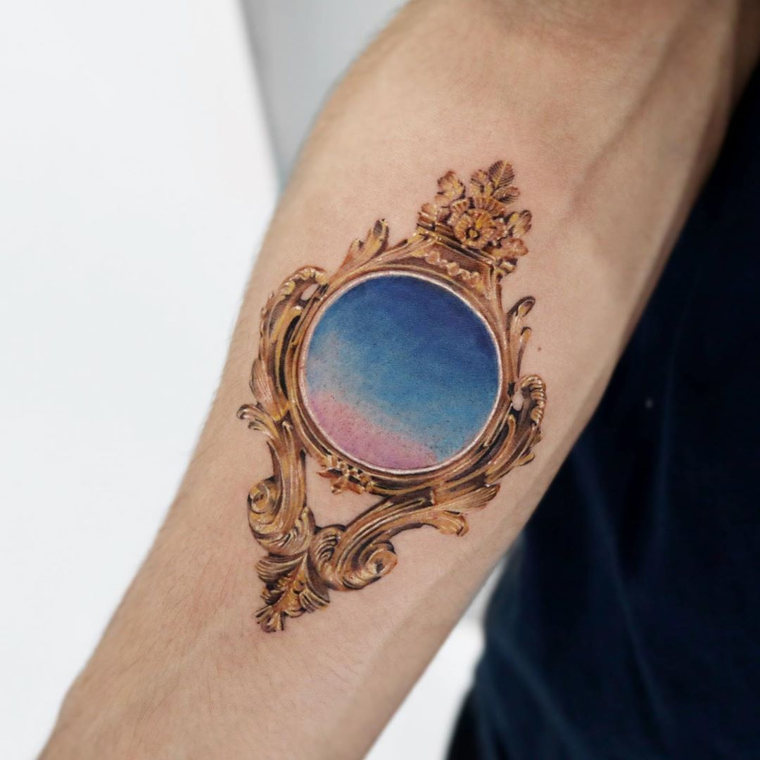 Antique frame tattoo by Mumi Ink
