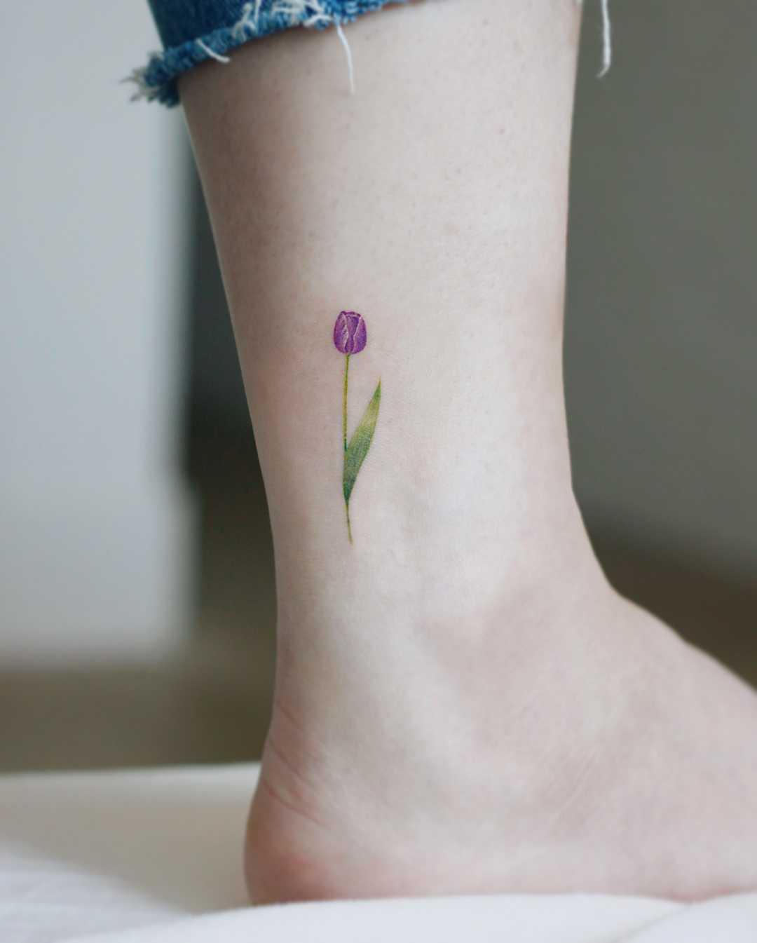 Purple tulip on an ankle by tattooist Saegeem