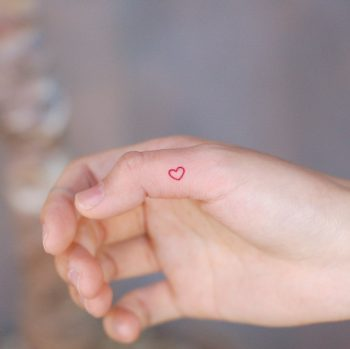 Red heart on a thumb by @wittybutton_tattoo