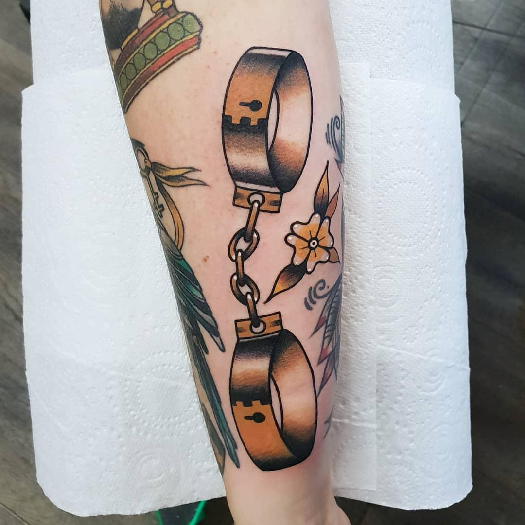 Golden shackles tattoo by @rabtattoo